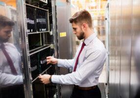 technician providing it service and inspecting server